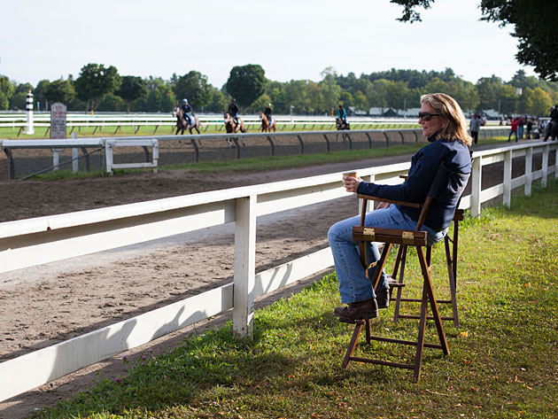 Equine  therapist, Carol Seaver carefully observes the horses  training on the  Saratoga race track.