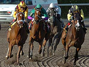 Bsharpsonata (green silks, 2nd from left) moves between horses on her way to victory in the Davona Dale.