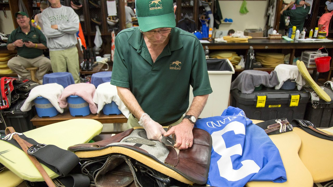 8512e313e4406 Valet Chuck Victory adds weights to a saddle behind the scenes in the  jockeys  room at Keeneland. Mark Mahan